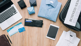 Business travel. Businessman getting ready to leave for a business trip and packing a bag with formal clothing, accessories, laptop and plane tickets, traveling Stock Photography