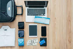 Business travel. Businessman getting ready to leave for a business trip and packing a bag with formal clothing, accessories, laptop and plane tickets, traveling Royalty Free Stock Images
