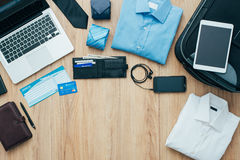Business travel. Businessman getting ready to leave for a business trip and packing a bag with formal clothing, accessories, laptop and plane tickets, traveling Royalty Free Stock Photography