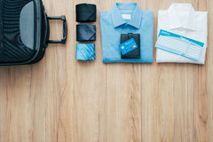 Business travel. Businessman getting ready to leave for a business trip and packing a bag with formal clothing, accessories and plane tickets, traveling and Stock Photography