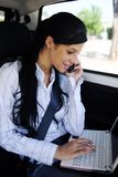 Business travel: businesswoman with laptop in car Royalty Free Stock Photo