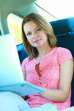Business travel: busy businesswoman with laptop in car Royalty Free Stock Images