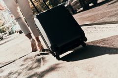 Business travel. Close up rear view of young woman pulling luggage while walking outdoors stock photo