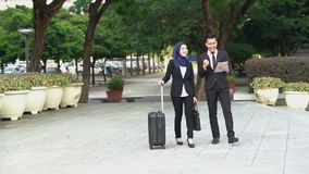 Business travel concept. Business people walking and discussing, using tablet pc outdoor stock footage