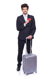 Business travel. Full length of a businessman standing with a luggage, showing blank credit card, over white background Royalty Free Stock Photography