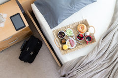 Business Travel Hotel Room with Breakfast in Bed. High Angle View of Breakfast Tray on Unmade Bed in Hotel Room in Business Trip Concept Image with Black stock image