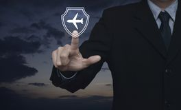 Business travel insurance and safety concept. Businessman pressing airplane with shield flat icon over sunset sky, Business travel insurance and safety concept royalty free stock image