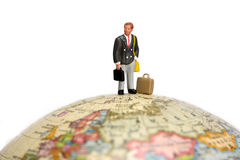 Business traveler. A miniature businessman stands alone on top of a globe against a white background. Taken with a Canon 5D Stock Photos