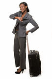 Business traveler. Full body of African American woman in grey business suit with black suitcase checking watch smiling standing on white Royalty Free Stock Images