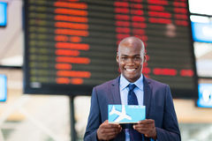 Business traveler airport. African business traveler in front of flight information board in airport Stock Photography