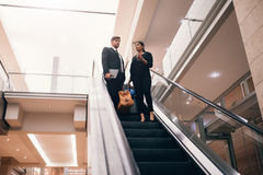 Business traveler with baggage on the escalator at the airport. Business men and women moving down with baggage on the escalator at the airport. Business Stock Photo