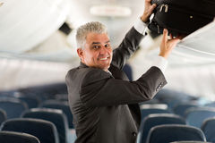 Business traveler luggage. Portrait of middle aged business traveler putting luggage into overhead locker on airplane Stock Images