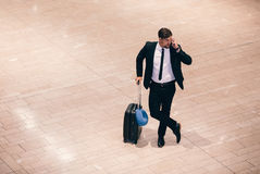 Business traveler making a phone call while waiting for flight Stock Photography