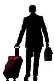Business traveler man walking rear view. Rear view one caucasian business traveler man walking with suitcase  full length silhouette in studio isolated white Stock Photography