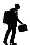 Business traveler man walking with suitcase. One caucasian business traveler man walking with suitcase on shoulders full length silhouette in studio isolated Royalty Free Stock Images