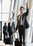 Business traveler pulling suitcase and gesturing. To co-worker Stock Photo