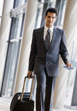Business traveler pulling suitcase and passport
