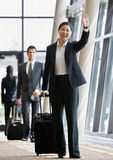 Business traveler pulling suitcase and waving. To co-worker Royalty Free Stock Image