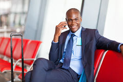 Business traveler talking. African business traveler talking on cell phone at airport Stock Image