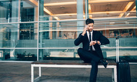 Business traveler talking on phone and checking time. Business traveler talking on mobile phone and looking at his watch.  Businessman sitting on bench making Royalty Free Stock Photography