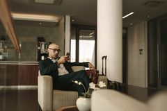 Business traveler waiting in airport lounge using phone. Business traveler waiting in airport lounge and using mobile phone. Businessman waiting for fight at Royalty Free Stock Photo