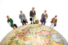 Business travelers. A group of miniature businessmen and businesswomen standing on a globe. Focus is on the man in the center with the others out of focus. Taken Royalty Free Stock Images