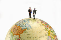 Business travelers. Two miniature businessmen figures stand on top of a globe set against a white background. Taken with a Canon 5D Stock Image