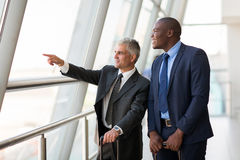 Business travelers pointing. Good looking business travelers pointing at airport Stock Image
