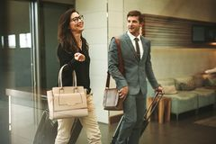 Business travelers walking through airport lobby. Two business travelers walking through airport lobby with their luggage and having a friendly chat. Businessman Royalty Free Stock Photo