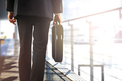 Business travelers walking in airport with luggage Stock Photos