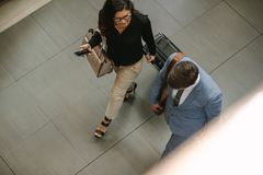 Business travelers walking together with luggage. Top view of two business travelers walking together with luggage and chatting. Business people arriving for a royalty free stock images