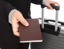 Business traveling pulling suitcase and holding passport Royalty Free Stock Photo