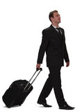 Business traveller. A young businessman carrying a roller suitcase, isolated against a white background Royalty Free Stock Photo