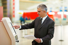 Business traveller airport. Mid age business traveller using self help check in machine at airport Stock Photography