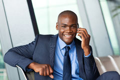 Business traveller cellphone. African business traveller talking on cellphone in airport Royalty Free Stock Images