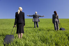 Business Travellers Find What They Are Looking For. Concept shot showing three business executives, one male and two female, walking through a green field Stock Photos