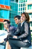 Business Trio. Three young business coworkers sitting outside an office building, one woman and two men Royalty Free Stock Photography
