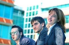 Business Trio 3 Blue Tint. Three young business coworkers, one woman and two men, outside an office building.  Blue tinted Stock Images