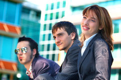 Business Trio 4. Three young business coworkers, one woman and two men, outside an office building Stock Photos
