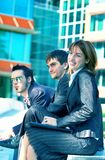 Business Trio Blue Tint. Three young businesspeople, one woman and two men, sitting outside an office building Royalty Free Stock Image