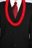 Business trip or business vacation. Business man in black suit wearing red power tie and hawaiian lei around neck stock image