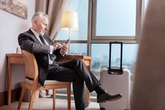 Senior glad businessman  ready to leave. Business trip. Happy confident serious man sitting on the chair while touching his phone and staring at it Royalty Free Stock Images