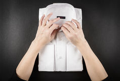 Business, trip, manufacturing, luggage and people concept. Close up of woman hands packing white shirt on black background Royalty Free Stock Photos