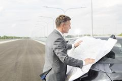 Mature businessman reading map while standing outside car on road royalty free stock images