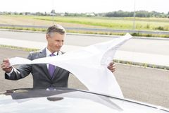 Mature professional analyzing map while standing outside car on road royalty free stock images