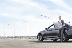 Mature professional with map standing outside car on road stock photo