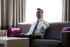 Businessman calling on smartphone at hotel room Royalty Free Stock Image