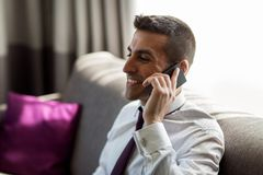 Businessman calling on smartphone at hotel room Royalty Free Stock Photography