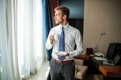 Business trip and people concept - businessman drinking coffee at hotel room. royalty free stock photography