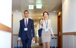 Business team with travel bags at hotel corridor. Business trip and people concept - men and women with travel bags and conference badges at hotel corridor Stock Photos